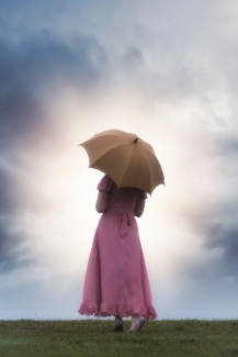 a woman in a pink dress with an umbrella