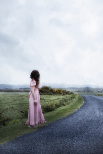 a woman in a long pink dress is waiting at the roadside